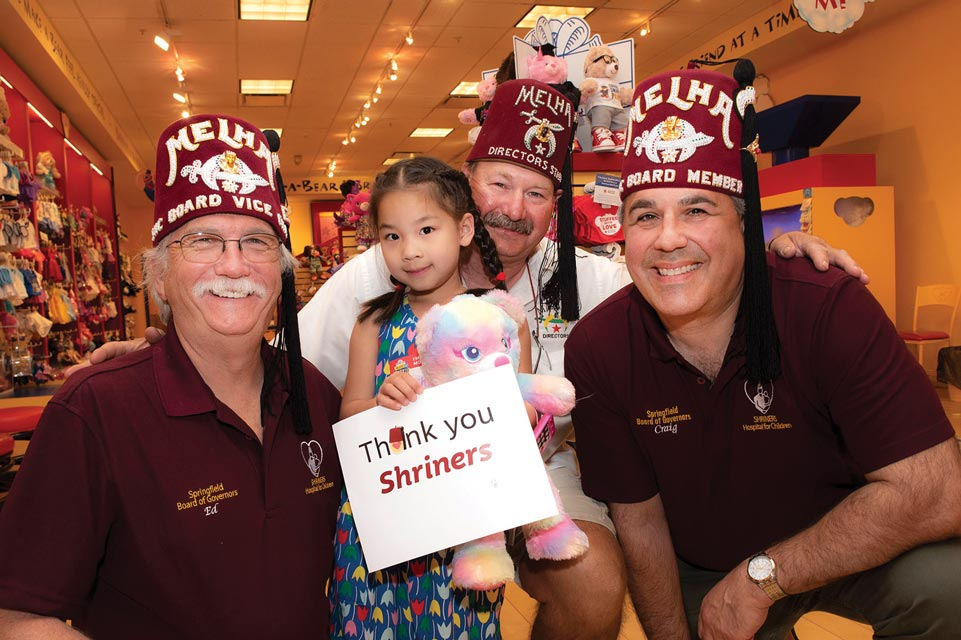 """Three Shriners wearing red fezzes with a little girl holding a stuffed animal and sign that says """"Thank you Shriners!"""""""