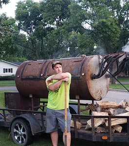 man in front of large bbq smoker drum