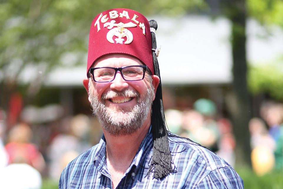 Smiling Shriner wearing a red fez