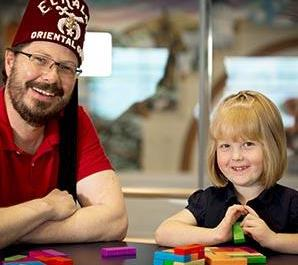shriner with patient helping